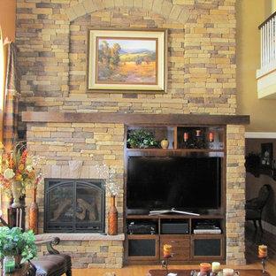 デンバーの大きいラスティックスタイルのおしゃれなLDK (フォーマル、黄色い壁、淡色無垢フローリング、標準型暖炉、石材の暖炉まわり、埋込式メディアウォール) の写真