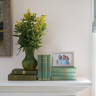 Modelo de salón cerrado, clásico, pequeño, sin televisor, con paredes blancas, suelo de madera en tonos medios, chimenea tradicional, marco de chimenea de piedra y suelo verde