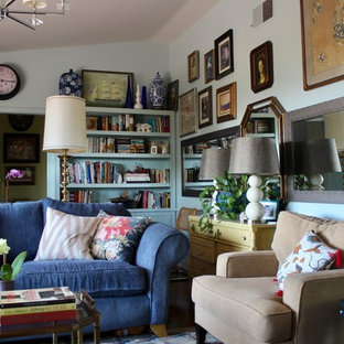 Mid-sized eclectic enclosed dark wood floor and brown floor living room library photo in San Diego with blue walls, a standard fireplace, a stone fireplace and a tv stand
