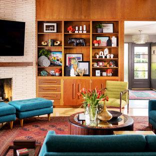Imagen de salón cerrado, vintage, grande, con paredes marrones, suelo de madera clara, chimenea tradicional, marco de chimenea de ladrillo, televisor colgado en la pared y suelo amarillo
