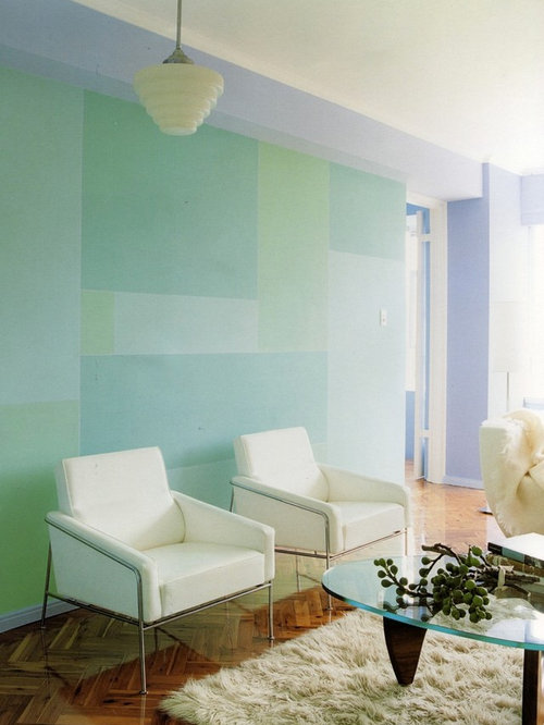 example of a trendy living room design in sydney with blue walls and medium tone hardwood