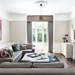 Photo of a medium sized classic enclosed living room in London with grey walls, dark hardwood flooring, a standard fireplace, a stone fireplace surround, a wall mounted tv and brown floors.