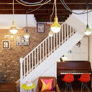 ロンドンの小さいエクレクティックスタイルのおしゃれなLDK (ミュージックルーム、マルチカラーの壁、濃色無垢フローリング) の写真
