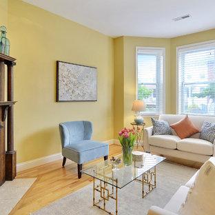 Foto di un piccolo soggiorno chic con pareti gialle, camino ad angolo, cornice del camino in legno e pavimento in legno massello medio