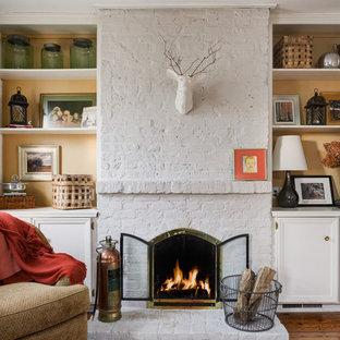 Repräsentatives, Fernseherloses, Abgetrenntes Klassisches Wohnzimmer mit braunem Holzboden, Kaminumrandung aus Backstein, gelber Wandfarbe und Kamin in Kolumbus
