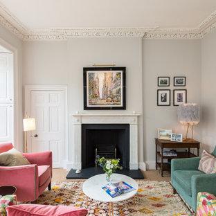 他の地域のトランジショナルスタイルのおしゃれなリビング (グレーの壁、カーペット敷き、標準型暖炉、ベージュの床) の写真