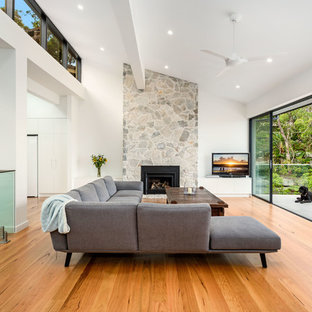 Modelo de salón abierto, actual, grande, con paredes blancas, suelo de madera en tonos medios, chimenea tradicional, marco de chimenea de piedra y televisor independiente