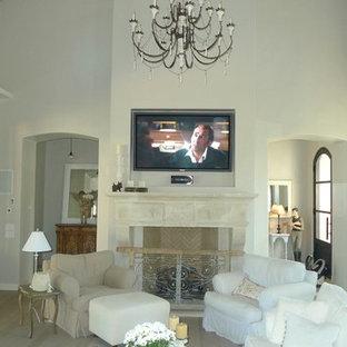 Aménagement d'un salon romantique de taille moyenne et ouvert avec un mur blanc, un sol en bois clair, une cheminée standard, un manteau de cheminée en pierre et un téléviseur fixé au mur.