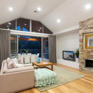 パースのビーチスタイルのおしゃれなLDK (白い壁、無垢フローリング、標準型暖炉、石材の暖炉まわり、据え置き型テレビ、ベージュの床) の写真