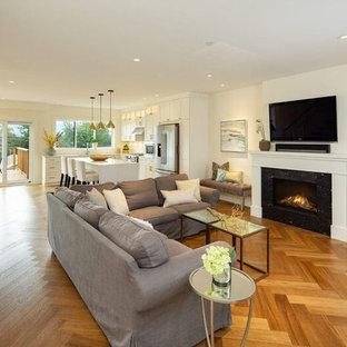 Esempio di un soggiorno classico di medie dimensioni e aperto con pareti bianche, camino classico, cornice del camino in metallo, TV a parete, pavimento marrone e pavimento in vinile