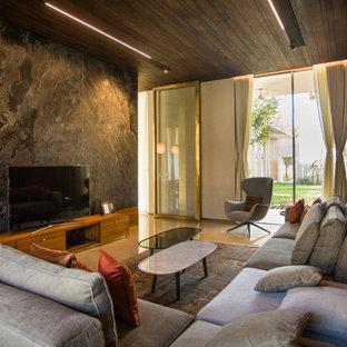 Foto de salón actual con paredes grises, suelo de cemento, televisor independiente y suelo beige