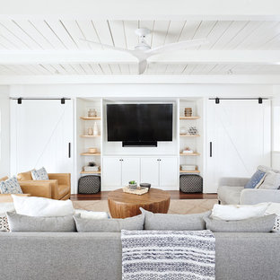 Living room - beach style dark wood floor and brown floor living room idea in San Francisco with white walls and a media wall