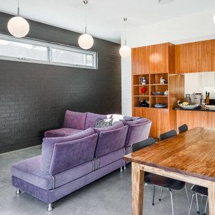 Cette image montre un salon design de taille moyenne et ouvert avec un mur blanc, béton au sol, aucune cheminée, un sol gris et un mur en parement de brique.