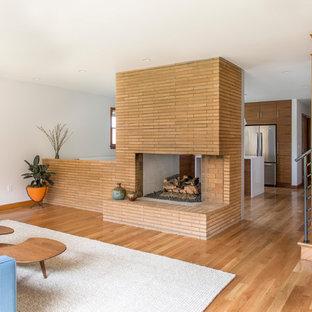 Mittelgroßes, Offenes Mid-Century Wohnzimmer mit weißer Wandfarbe, braunem Holzboden, Tunnelkamin, Kaminumrandung aus Backstein und verstecktem TV in Portland