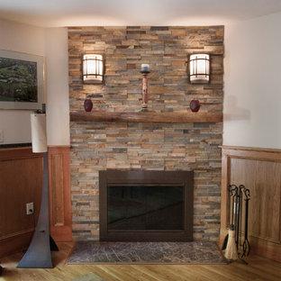 Esempio di un soggiorno tradizionale aperto con pareti beige, parquet chiaro, camino ad angolo, cornice del camino in pietra e pavimento marrone