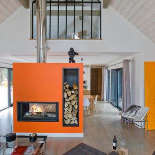 Modelo de salón abierto, contemporáneo, de tamaño medio, sin televisor, con parades naranjas, suelo de madera en tonos medios y chimenea de doble cara