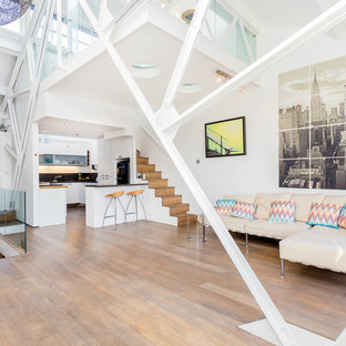 This is an example of a contemporary mezzanine living room in London with white walls, medium hardwood flooring and brown floors.