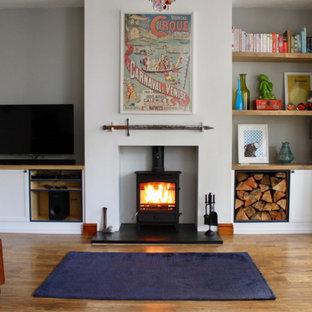 Esempio di un soggiorno stile rurale di medie dimensioni e chiuso con pareti grigie, pavimento in laminato, stufa a legna, cornice del camino in intonaco, parete attrezzata e pavimento marrone