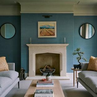 Großes, Repräsentatives, Fernseherloses Klassisches Wohnzimmer mit blauer Wandfarbe, Teppichboden, Kamin und Kaminumrandung aus Stein in Wiltshire