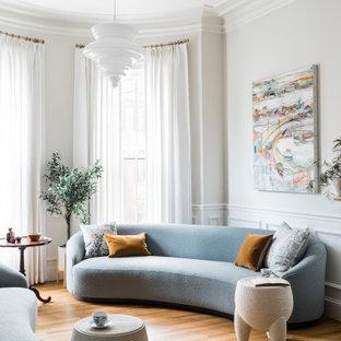Idée de décoration pour un salon design avec un mur blanc, un sol en bois brun, un sol marron et boiseries.