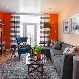 Modelo de salón abierto, contemporáneo, pequeño, sin chimenea, con parades naranjas y suelo de madera clara