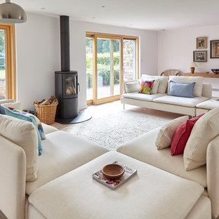 Ejemplo de salón para visitas actual, grande, sin televisor, con paredes blancas, suelo de madera clara, estufa de leña y marco de chimenea de metal