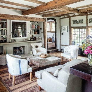 Inspiration for a medium sized rustic enclosed living room in London with white walls, dark hardwood flooring, brown floors, a standard fireplace and a stone fireplace surround.