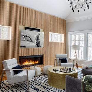 Inspiration för moderna vardagsrum, med grå väggar, mellanmörkt trägolv, en bred öppen spis, en spiselkrans i trä, en väggmonterad TV och brunt golv