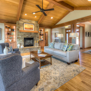 Large arts and crafts formal open concept living room in Other with beige walls, medium hardwood floors, a standard fireplace, a stone fireplace surround and no tv.
