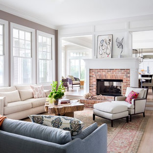 Immagine di un grande soggiorno american style aperto con sala formale, parquet chiaro, camino bifacciale, cornice del camino in mattoni, nessuna TV e pavimento marrone