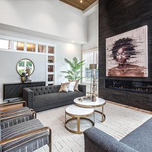 Modern inredning av ett vardagsrum, med vita väggar, mellanmörkt trägolv, en bred öppen spis och brunt golv