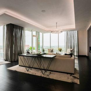 Diseño de salón abierto, contemporáneo, grande, con suelo de madera oscura, chimenea tradicional, marco de chimenea de baldosas y/o azulejos y suelo negro