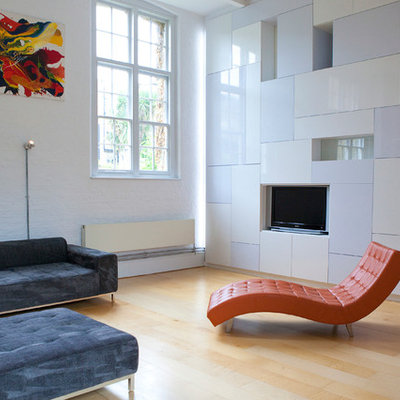 Example of a mid-sized trendy formal and enclosed living room design in London with white walls and a media wall