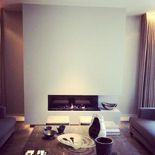 チェシャーの大きいコンテンポラリースタイルのおしゃれな独立型リビング (フォーマル、白い壁、濃色無垢フローリング、コーナー設置型暖炉、漆喰の暖炉まわり、テレビなし) の写真
