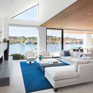 ロサンゼルスの大きいコンテンポラリースタイルのおしゃれなLDK (白い壁、横長型暖炉、フォーマル、コンクリートの床、テレビなし、白い床) の写真
