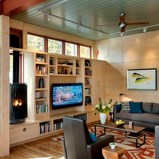 Example of a trendy medium tone wood floor living room design in Burlington with a media wall and a wood stove