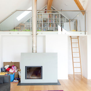 Danish light wood floor living room photo in Cornwall with white walls and a standard fireplace