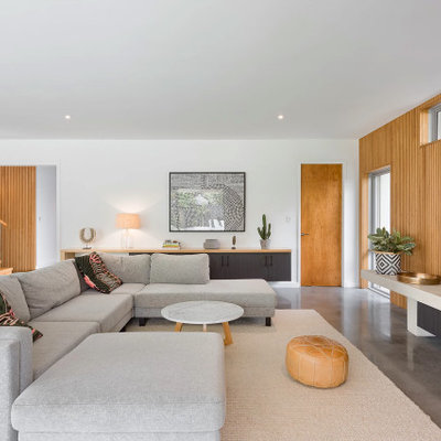 Mid-sized trendy open concept concrete floor and gray floor living room photo in Perth with no fireplace, a wall-mounted tv and white walls