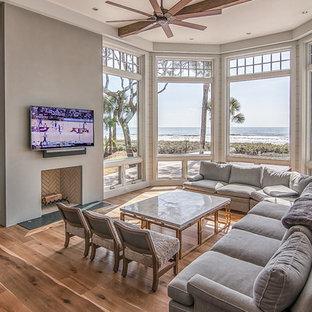 アトランタの中サイズのビーチスタイルのおしゃれな独立型リビング (ベージュの壁、淡色無垢フローリング、標準型暖炉、埋込式メディアウォール、フォーマル、コンクリートの暖炉まわり、茶色い床) の写真