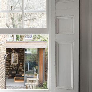 Modelo de salón abierto, casetón y panelado, actual, pequeño, panelado, con paredes grises, suelo de baldosas de cerámica, estufa de leña, marco de chimenea de yeso, suelo gris y panelado