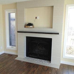 Modelo de salón para visitas abierto, contemporáneo, de tamaño medio, con paredes amarillas, suelo de madera oscura, chimenea tradicional y marco de chimenea de baldosas y/o azulejos