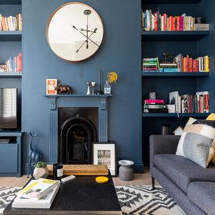 Idéer för mellanstora funkis separata vardagsrum, med blå väggar, ljust trägolv, en spiselkrans i trä, ett bibliotek, en standard öppen spis, en fristående TV och beiget golv