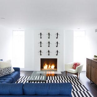 Idee per un soggiorno minimal di medie dimensioni e aperto con sala formale, pareti bianche, parquet scuro, camino classico, TV a parete, cornice del camino in intonaco e pavimento nero