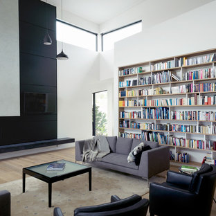 Living room library - contemporary open concept medium tone wood floor and brown floor living room library idea in Portland with white walls and a wall-mounted tv
