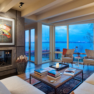 Example of a trendy medium tone wood floor living room design in Seattle with a two-sided fireplace