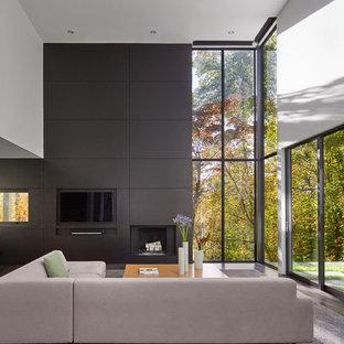 Ispirazione per un soggiorno contemporaneo aperto con pareti bianche, camino classico, TV a parete e pavimento nero