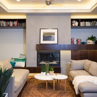 Modern inredning av ett stort allrum med öppen planlösning, med grå väggar, mörkt trägolv, en standard öppen spis och en spiselkrans i gips