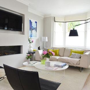 Immagine di un soggiorno minimal aperto con pareti grigie, parquet chiaro, camino lineare Ribbon, TV a parete e cornice del camino in intonaco
