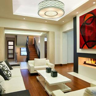 Immagine di un soggiorno minimal aperto con sala formale, pareti beige, pavimento in legno massello medio e camino bifacciale