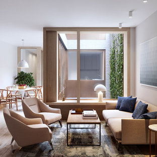 This is an example of a medium sized contemporary enclosed living room in London with grey walls, light hardwood flooring and beige floors.
